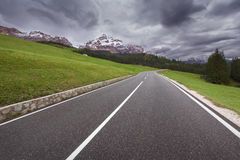 Dramatic scenery with road towards the heavy clouds Stock Photos
