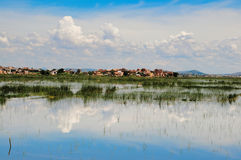 Dramatic scenery of a village in high land Madagascar. Sky with dramatic clouds above a Malagasy typical village and flooded plain which reflect the cloudy blue Stock Photos
