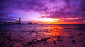 Dramatic scenic sunset. Vivid sunset over ocean at pier in the Caribbean royalty free stock photo