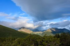 Dramatic scenic view, cloudy sky and early evening sun highlighting mountain peaks, Cerro Alarken Nature Reserve, Ushuaia, Argenti. Na royalty free stock photos