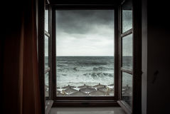 Dramatic sea view from opened window with big stormy waves and dramatic sky during rain and storm weather in fall season on sea co. Dramatic sea view from opened stock photography