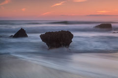 Dramatic seascape blurry waves. Stones during sunset. Royalty Free Stock Photography