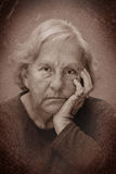 Dramatic senior woman sulking portrait. Dramatic grungy noisy almost black and white portrait of a real senior woman sulking, looking at camera Royalty Free Stock Images