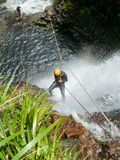 Waterfall Abseil. Dramatic shot of a Abseiler rappelling through a waterfall in the Coromandel Mountains Stock Images