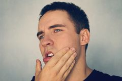Dramatic Shot of a Man in Pain holding his Jaw. Toothache. A punch in the jaw Slap. Insult. The guy strokes his chin after shaving. Dramatic Shot of a Man in royalty free stock images
