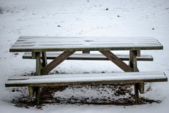 Wooden bench in the winter snow stock image