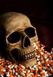 Dramatic sickness. Dramatic skull in the pile of drugs symbolises sickness and danger of abuse stock image