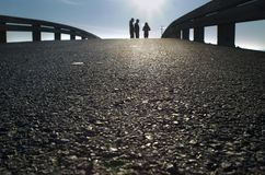 Dramatic Silhouette. Silhouette of three people standing on a bridge with detail of asphalt Stock Image