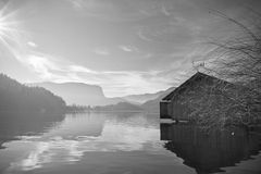 Dramatic silhouette of wooden boathouse on pure lake bled in direct sunlight and reflection in water in winter. Scenic landscape by wooden boathouse floating on stock images