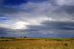 Dramatic Sky. Small house in the distance of a wide open flat landscape with approaching storm Stock Photos