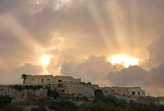Dramatic Sky Above A Fortress, Malta. Sunbeams breaking through the clouds in M`Garr, Gozo, Malta Royalty Free Stock Image
