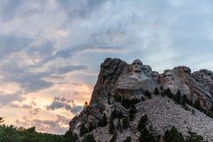 A dramatic Sky Behind Mount Rushmore. A dramatically colorful sky developing around sunset behind the four US presidents of Mount Rushmore, in North Dakota stock photography