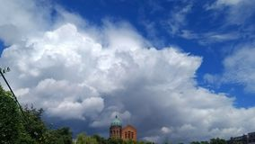 Dramatic sky. Big clouds over a church tower. Michaelskirche in Berlin, Germany Royalty Free Stock Photography