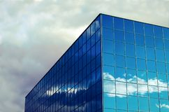 Dramatic sky blue office building finance window corner glass clouds reflections. Blue glass window office building corner sky royalty free stock photos