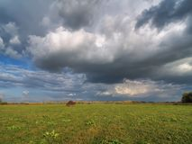 Dramatic sky with clouds and haystack. Dramatic sky with clouds over a field with a haystack Stock Image