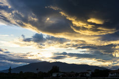 Dramatic sky with dark clouds above the mountain at sunset. Stock Photography