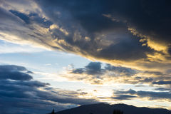Dramatic sky with dark clouds above the mountain at sunset. Stock Photo