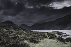 Dramatic sky with dark clouds over scenic mountain valley in Lake District, England. Dramatic sky with dark clouds over scenic mountain valley with lake in Lake stock photo