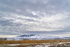 Dramatic sky filled with cottony clouds over a scenic landscape in winter. A lake and snow capped mountain cna be seen beyond the vast grassy terrain stock image