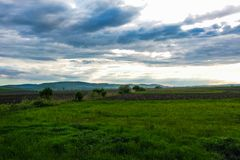 Dramatic sky and green meadows, in the distance one can see mountains, nature background.  royalty free stock images