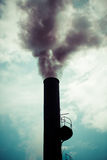 Dramatic sky with industrial chimney from a Palm oil plantation Royalty Free Stock Photography