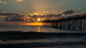 Dramatic sky lights up the clouds with an orange glow as fishermen cast their lines from the end of an old wooden pier at sunrise. stock photos