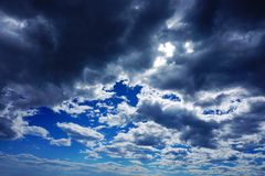 Dramatic sky with many rain clouds which cover a blue sky. Grayish and blue dramatic rain clouds which cover clearly blue sky, cloudscape, light, dark, landscape royalty free stock photography