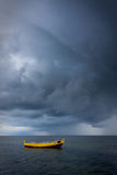 Dramatic sky over boat in sea Stock Image