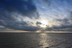 Dramatic sky over a dark sea. Stock Photos