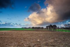 Dramatic sky over field Stock Photos