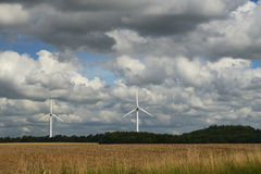 Dramatic sky over field and windmills. Textured sky with storm clouds over the field and two windmills Stock Photos