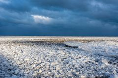 Dramatic sky over frozen winter beach landscape. Snow and sand and dramatic light over Lake Michigan shore in January stock photo