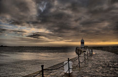Dramatic sky with path to the Lighthouse. In Castletown on the Isle of Man Royalty Free Stock Photos
