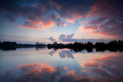 Dramatic sky reflected in lake at sunrise Stock Photography