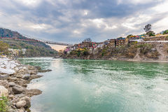 Dramatic sky at Rishikesh, holy town and travel destination in India. Colorful sky and clouds reflecting over the Ganges River. Royalty Free Stock Images