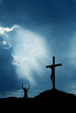 Dramatic sky scenery with cross and a worshiper vertical image Royalty Free Stock Photos