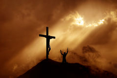 Dramatic sky scenery with a mountain cross and a worshiper Stock Photos