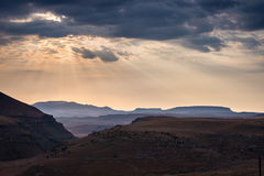 Dramatic sky, storm clouds and sun rays glowing over valleys, canyons and table mountains of the majestic Golden Gate Highlands Na Royalty Free Stock Photos