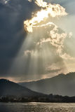 Dramatic sky with sun rays over the sea Stock Photography
