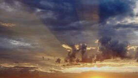 Dramatic sky with sun rays seep through clouds during sunrise. Timelapse stock footage