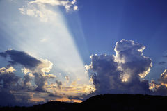 Dramatic sky with sunbeams and dynamic clouds at sunset Stock Image