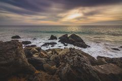 Cloudy Point Dume Sunset. Dramatic sky at sunset along Point Dume State Beach with waves crashing into rock formations along the beach, Malibu, California Royalty Free Stock Photos
