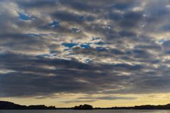 Dramatic sky at sunset over the lake with forest at horizon. Malente, Germany stock photography