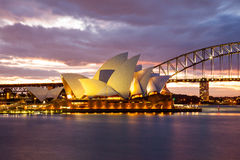 Dramatic sky and the Sydney Opera House. Sydney, Australia - July 11, 2010; Sydney Opera House and the Harbour Bridge at dusk. Taken from Mrs. Macquarie's Point royalty free stock images