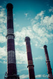 Dramatic sky and three industrial chimneys Royalty Free Stock Photography