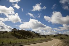 Dramatic Sky and a turn in the road. Shot of a dramatic sky and a turn in a country road royalty free stock images