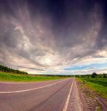 Dramatic sky under country asphalt road. Royalty Free Stock Photos