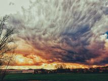 Dramatic sky with upcoming bad weather and black clouds as the sun goes through the clouds and creates the wonderfully colorful sk. Climate change and frequent royalty free stock photo