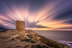 Dramatic sunset at Punta Spanu on the coast of Corsica. Dramatic slow shutter image of sun setting behind the ancient Genoese tower at Punta Spanu near Lumio Royalty Free Stock Images