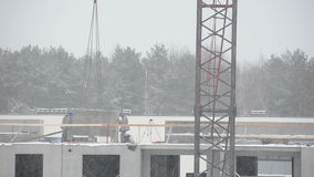 Dramatic snow fall and construction site builders in winter. Dramatic blizzard snow fall and construction site workers builders work in winter season. Static stock footage